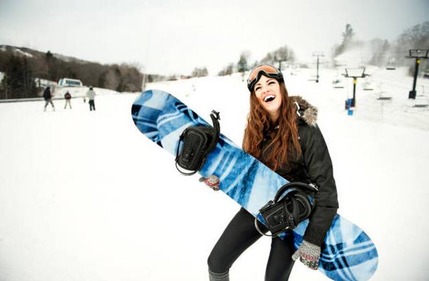 Femme sur une piste de ski qui tient à skateboard en souriant