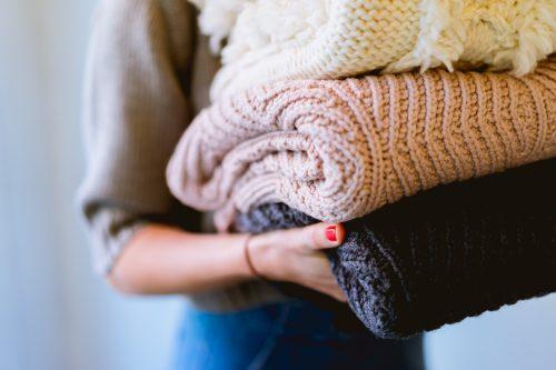 femme portant 3 pulls en maille