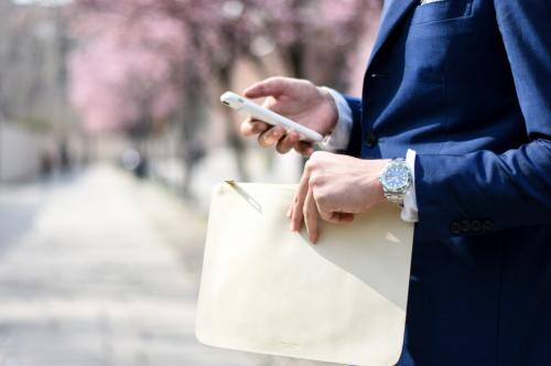 Homme habillé en costard avec un portable et une montre Rolex