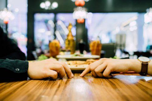 Deux personnes sur le point de se toucher la main dans un restaurant