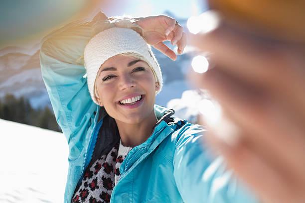 Femme qui se prend en selfie à la montagne, avec une veste de ski bleue et un pull à motifs léopard