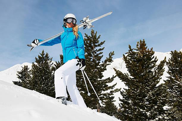 Femme en pantalon fuseau blanc et veste de ski cintrée bleue qui porte ses skis sur ses épaules