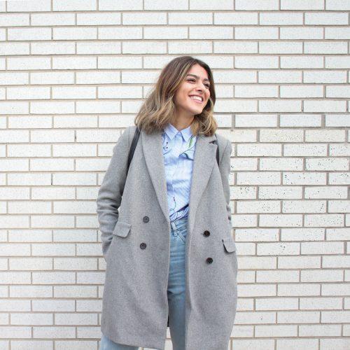 femme portant un jean une chemise bleue et un manteau long gris clair devant un mur en briques blanches
